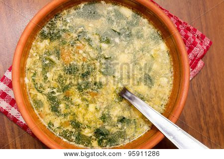 Top view of a chard soup in a rustic clay bowl on a wooden table
