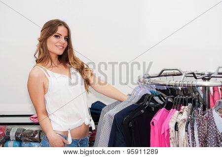 Beautiful teenage girl looking wardrobe in a boutique