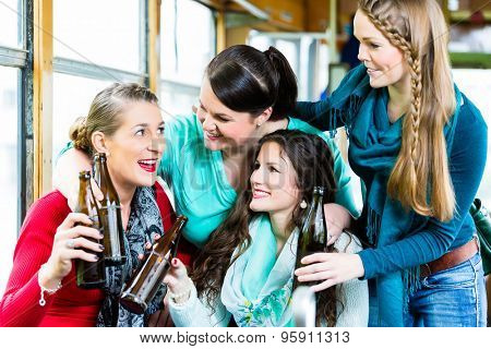 Group of people in tram bar having beer party in public transport