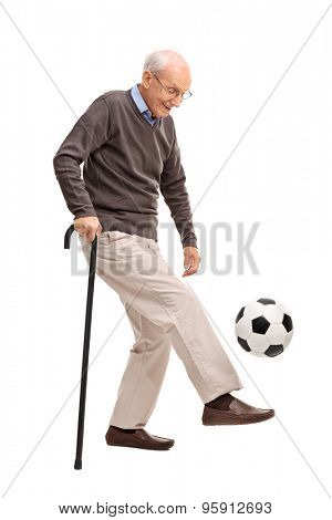 Full length profile shot of a senior gentleman with a cane juggling a football isolated on white background
