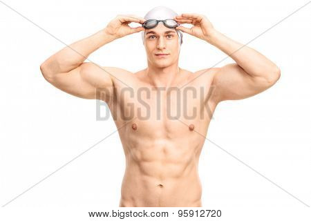 Muscular young swimmer with a gray swim cap and black swimming goggles looking at the camera and smiling isolated on white background