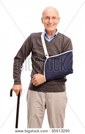 Vertical shot of a senior gentleman with a broken arm smiling and looking at the camera isolated on white background