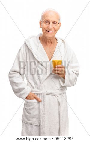 Vertical shot of a cheerful senior in a white bathrobe holding an orange juice and looking at the camera isolated on white background