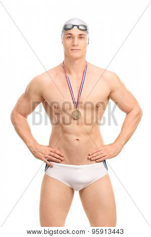 Vertical shot of a young handsome swimming champion in white swim trunks isolated on white background