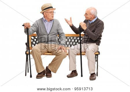 Studio shot of a two senior gentlemen having a conversation seated on a wooden bench isolated on white background