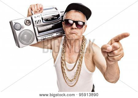 Grumpy senior rapper carrying a ghetto blaster on his shoulder and pointing with his finger isolated on white background