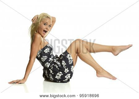 Young blond woman wearing a flower dress isolated on a white background