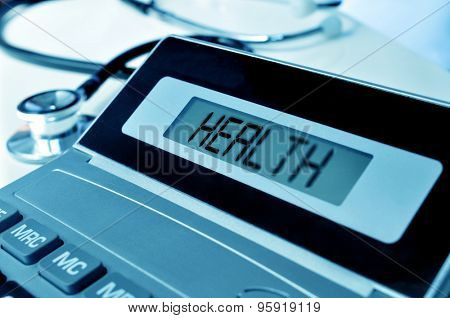 closeup of an electronic calculator with the word health in its display and a stethoscope, depicting the concept of the healthcare business