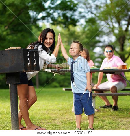 mother and son high fiver beside barbecue grill at picnic