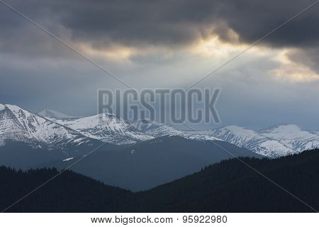 Spring landscape with stormy sky. Last snow on the mountain tops. A ray of sunlight from the clouds. Carpathian Mountains, Ukraine