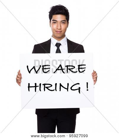 Businessman hold with white card board presenting phrase of we are hiring