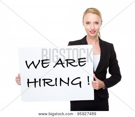 Caucasian businesswoman hold white board with phrase of we are hiring