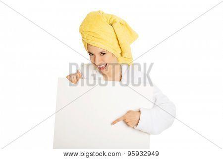 Spa woman in bathrobe holding empty banner.
