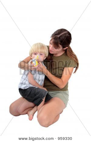 Young Mother Giving Respiratory Medicine To Her Son