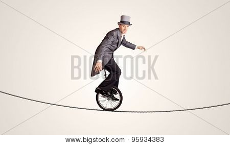 Extreme business man riding unicycle on a rope concept on background