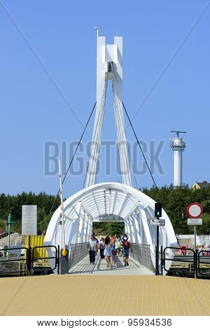 USTKA - JULY 07: Tourists pass on a rotating bridge on the Slupia River from one part of town to another on 7 July 2015 in Ustka, Poland.