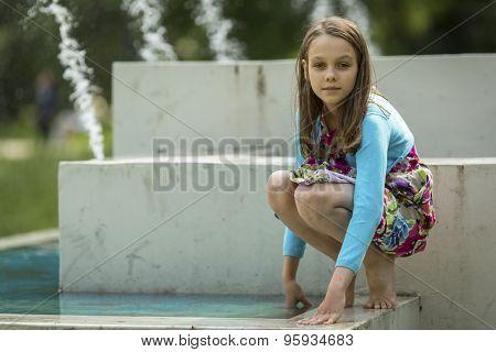 Cute girlie plays near the city fountain.