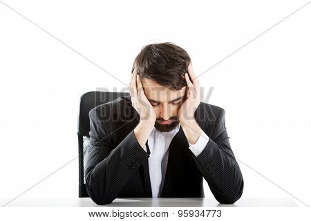 Tired businessman sitting at the desk.