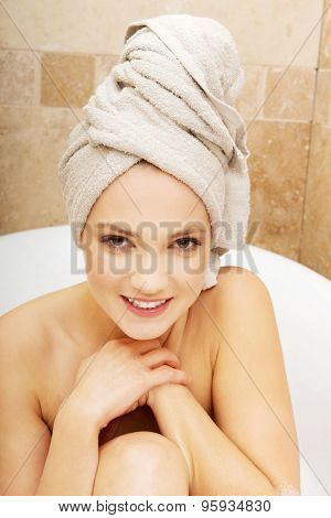 Young spa woman sitting in bathtub.
