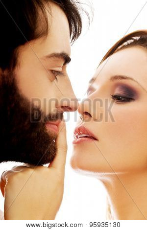 Young woman putting her finger on man's lips.
