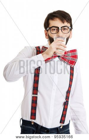 Funny man wearing suspenders drinking milk.