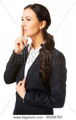 Beautiful businesswoman making silent sign.