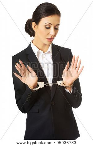 Full length businesswoman with handcuffs.