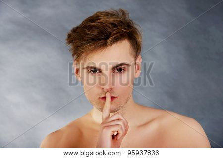 Young handsome man with finger on lips.