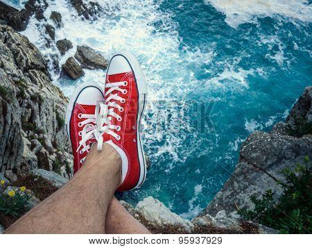 Men's feet on the cliff