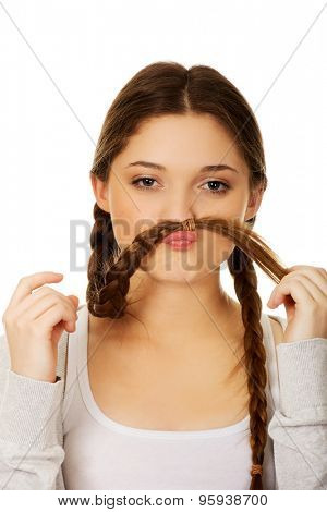 Happy teenage woman making moustache from hair.