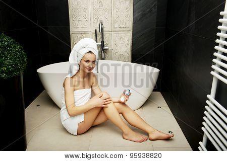 Beautiful woman applying cream on leg in bathroom.
