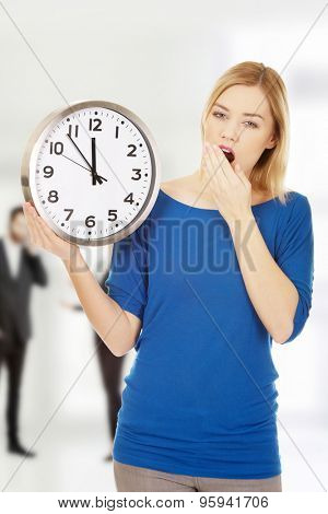 Young yawning woman holding a clock.