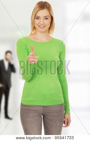 Young casual woman pointing at camera.
