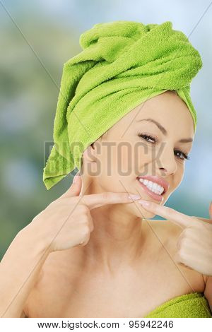 Beauty woman squeezing pimple on cheek.