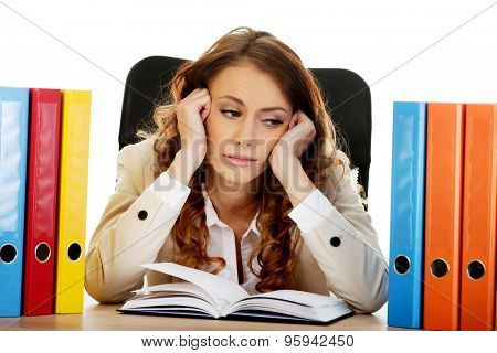 Exhausted businesswoman with binders by a desk.