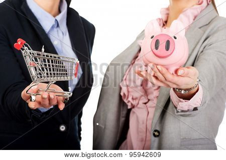 Two businesswomen holding a piggybank and shopping cart.