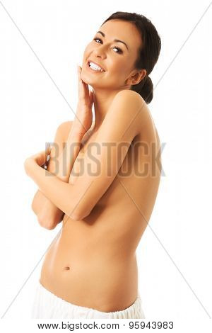 Topless woman wrapped in towel touching chin.