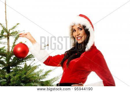Smiling santa woman decorating christmas tree.
