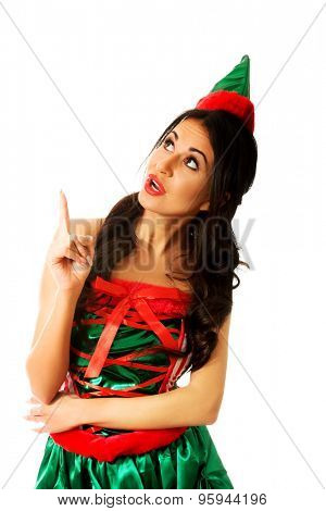 Surprised woman wearing elf clothes pointing up.
