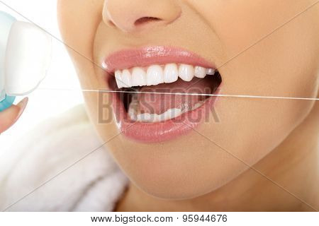 Beautiful woman using dental floss.