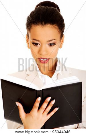 Shocked african businesswoman with a notebook.