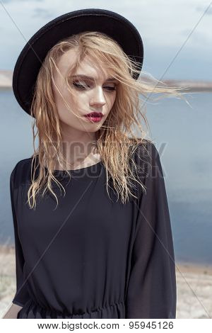 fashion photo of young beautiful sexy girl with wet hair in a black hat and a black cotton dress