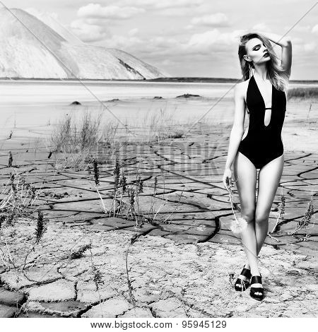 beautiful sexy cute girl in a fashion shoot in a bathing suit in desert dry cracked earth