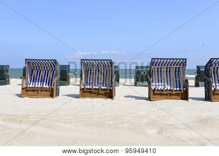 Empty sunbathing chairs on the beach.