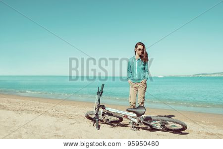 Girl standing with a bicycle on beach