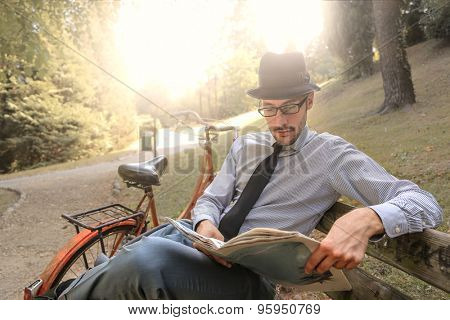 Man reading the newspaper at the park