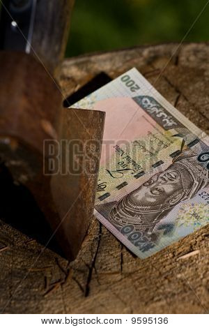 A Naira Banknote Being Cut With An Axe