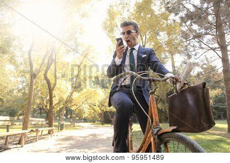 Shouting businessman riding a bike