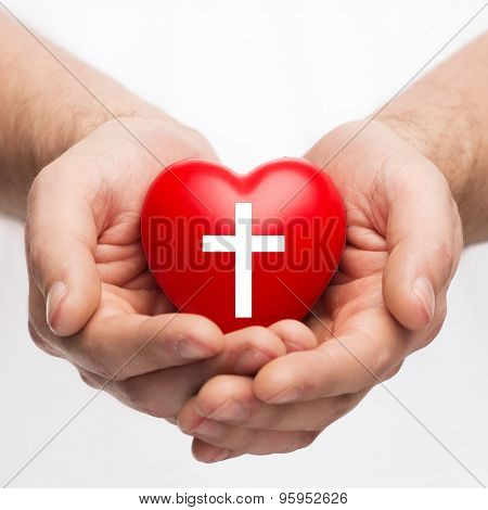 religion, christianity and charity concept - male hands holding red heart with christian cross symbol