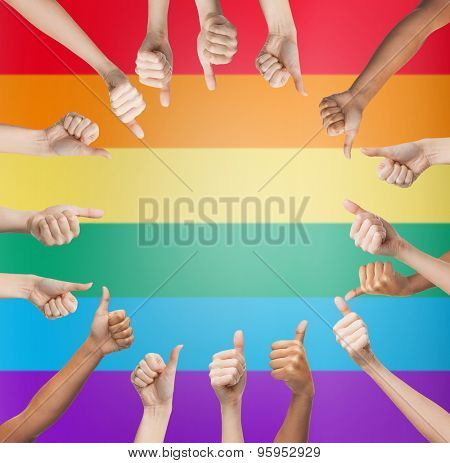 people, gay pride, gesture and homosexual concept - human hands showing thumbs up in circle over rainbow flag stripes background
